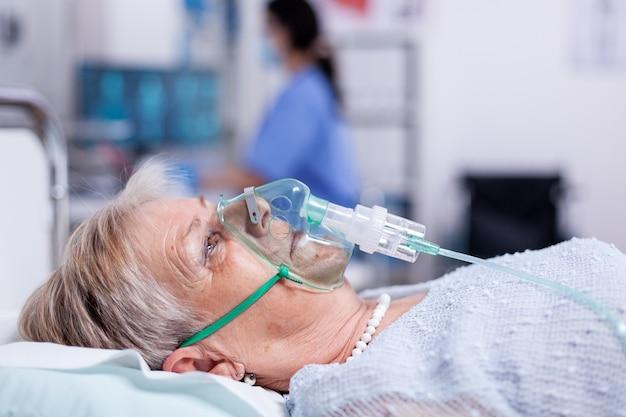 Vieille femme respirant avec un masque à oxygène allongée dans un lit d'hôpital recevant un traitement pour une infection par le coronavirus