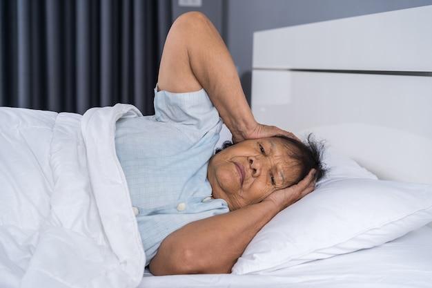 Vieille femme souffrant d'insomnie essaie de dormir dans son lit