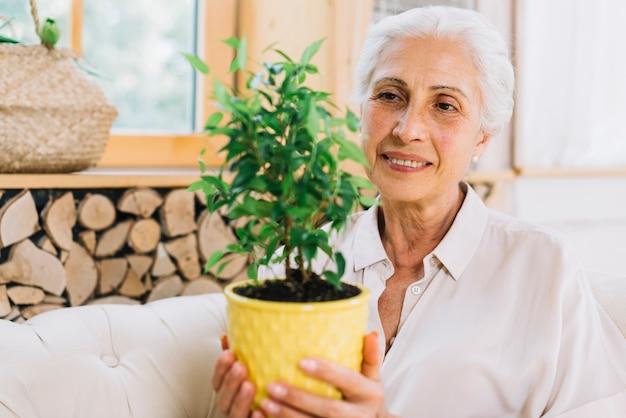 Une vieille femme souriante tenant une plante en pot