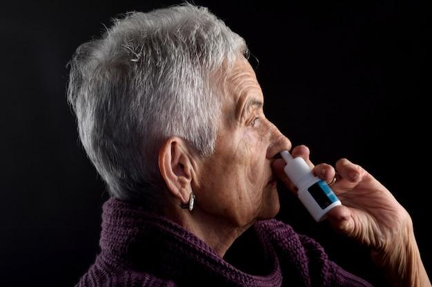 Vieille femme avec spray nasal
