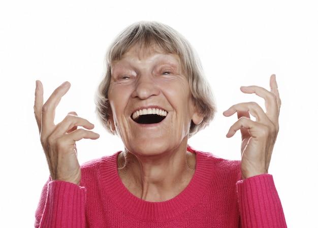 Vieille femme surprise heureuse sur fond blanc, concept de mode de vie