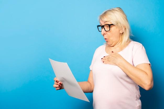 Vieille femme sympathique dans un t-shirt décontracté et des lunettes tenant une feuille de papier dans ses mains et le regardant avec un visage surpris sur un mur bleu isolé. visage émotionnel. lettre de concept, avis