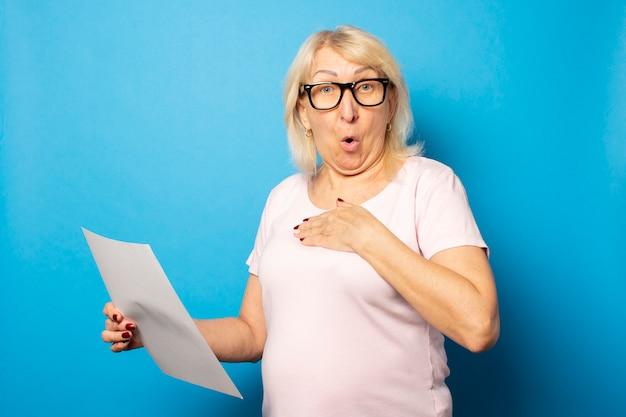 Vieille femme sympathique en t-shirt décontracté et lunettes tenant une feuille de papier dans ses mains avec un visage surpris sur un mur bleu isolé. visage émotionnel. lettre conceptuelle, préavis, surprise, choc