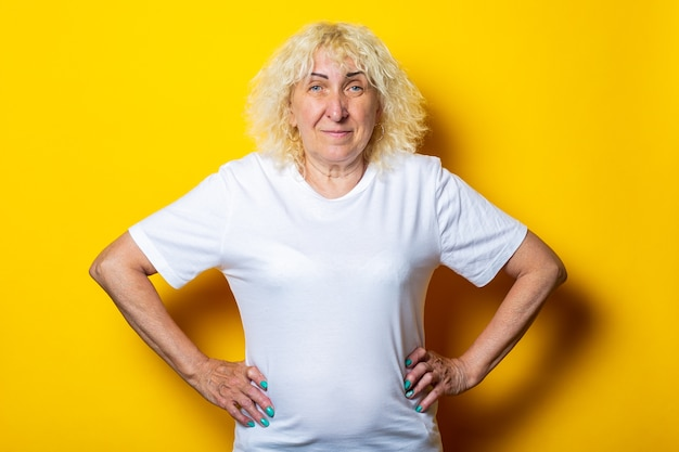Vieille femme en t-shirt blanc décontracté sur mur jaune.