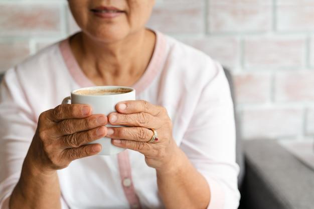 Vieille femme tenir une tasse de café chaud à la maison