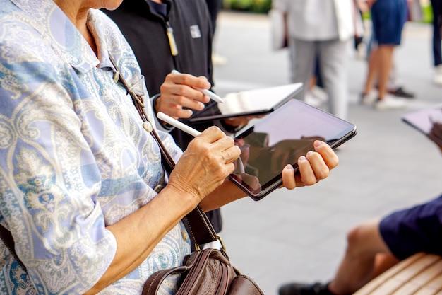 Vieille femme teste et apprend à utiliser un stylo électrique avec tablette
