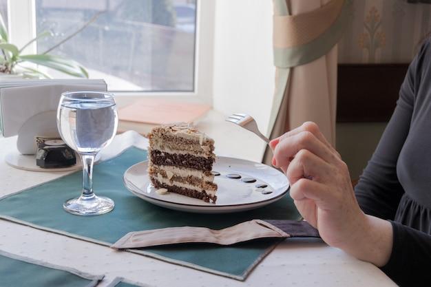 Une vieille femme tient une fourchette dans sa main et mange une tranche de gâteau aux noix dans un café