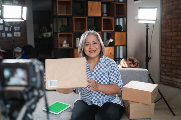 Vieille femme vlogger enregistre une vidéo de déballage