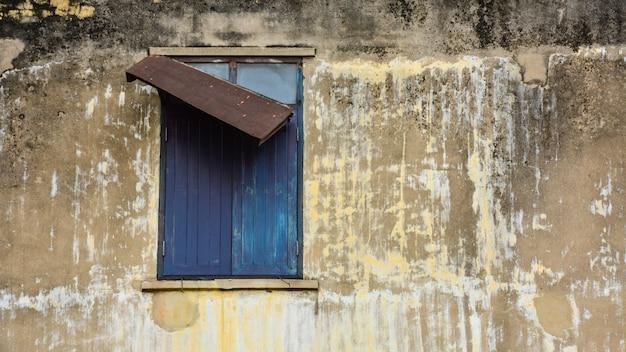 Vieille fenêtre en bois marron dans des bâtiments en béton abandonnés.