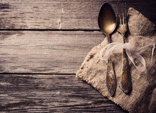 Vieille fourchette et cuillère sur fond de bois