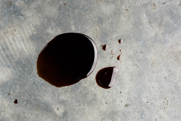 Vieille fuite de voiture automobile noire ou goutte à goutte sur le sol en béton sur la vue de dessus