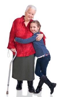 Vieille grand-mère avec petite-fille qui pose en studio sur fond blanc