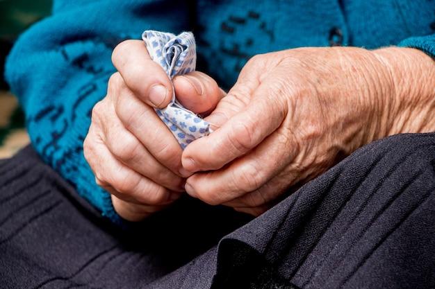 Une vieille grand-mère tient un mouchoir dans ses mains. les mains d'une vieille femme