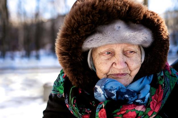 Vieille grand-mère triste enveloppée dans un châle regardant au loin