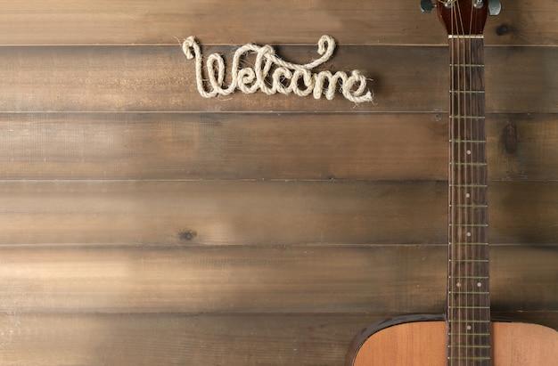 Vieille guitare et texte de bienvenue sur bois