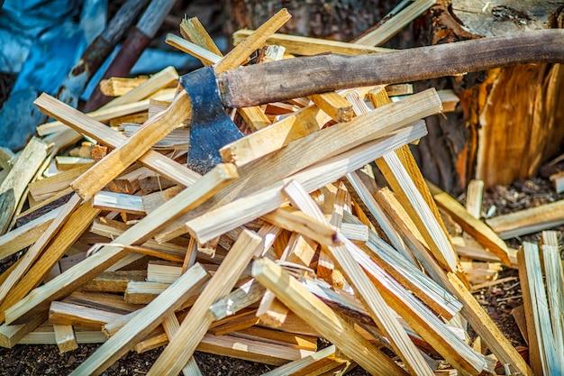 Vieille hache sur le bloc de bois avec un tas de bûches de bois coupées sur le sol.