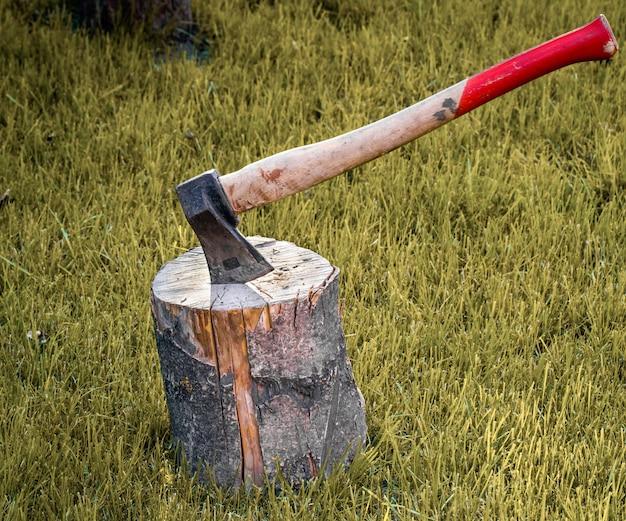Vieille hache rouillée coincée dans une bûche de bois sec
