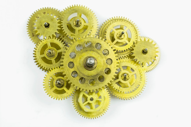 Vieille horloge au ralenti faite d'engrenages en bronze isolés sur fond blanc.