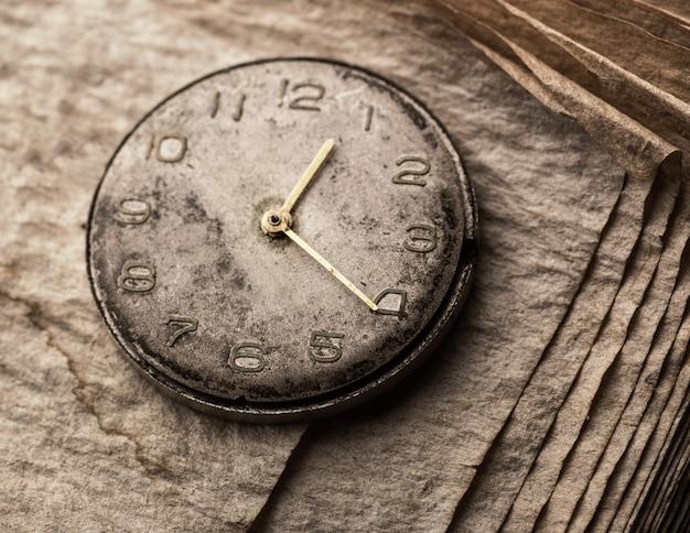 Vieille horloge sur un livre manuscrit