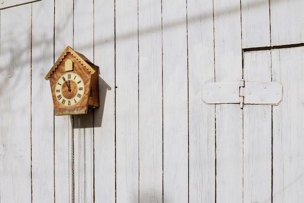 Vieille horloge sur un mur clair en bois. horloge ancienne. coucou