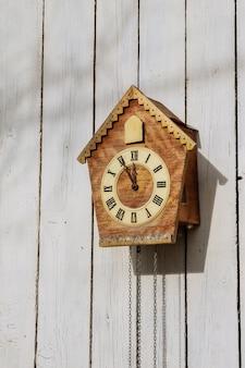 Vieille horloge sur un mur clair en bois. horloge ancienne.