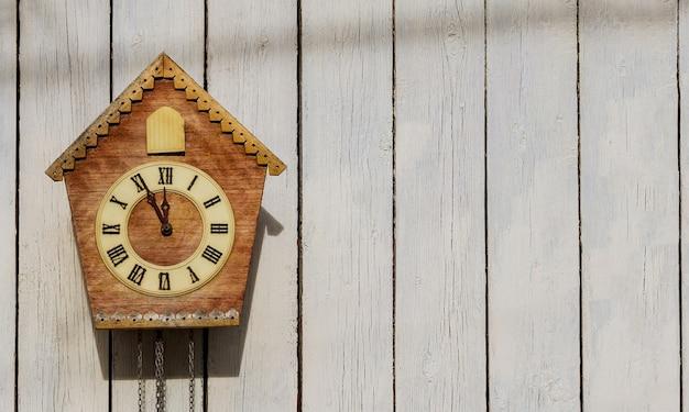 Vieille horloge sur un mur lumineux en bois. horloge vintage. coucou. espace copie.