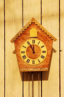 Vieille horloge sur un mur lumineux en bois. horloge vintage. coucou