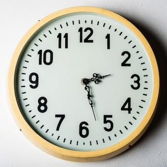 Vieille horloge ronde sur le mur blanc