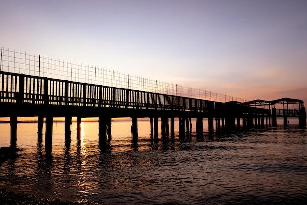 Une vieille jetée délabrée avec des planches cassées, lors d'un magnifique coucher de soleil sur un lac tranquille.