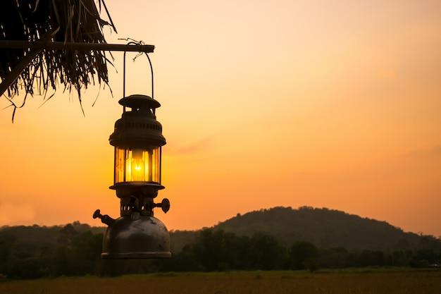 Vieille lanterne accrocher un bois au coucher du soleil