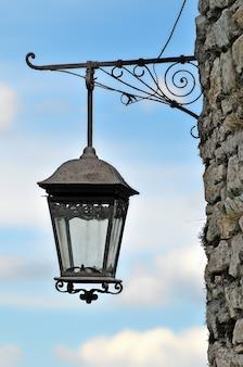 Vieille lanterne sur le mur de pierre de l'ancien château contre le dos