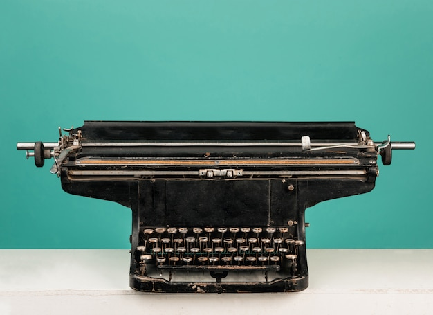 Vieille machine à écrire rétro avec du papier sur la table en bois