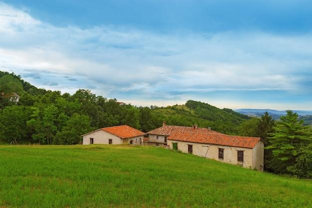 Vieille maison abandonnée en décomposition dans la campagne italienne se tient sur l'herbe verte parmi les arbres.