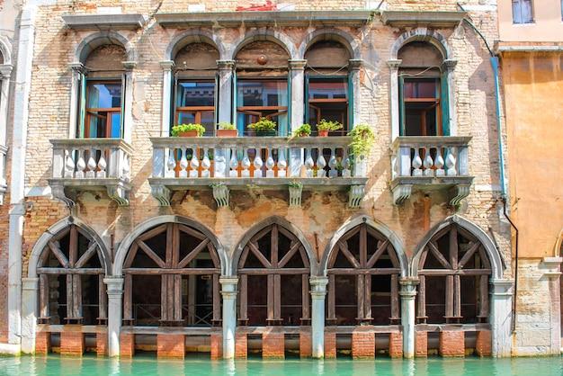 Vieille maison avec arches et balcon près du canal à venise