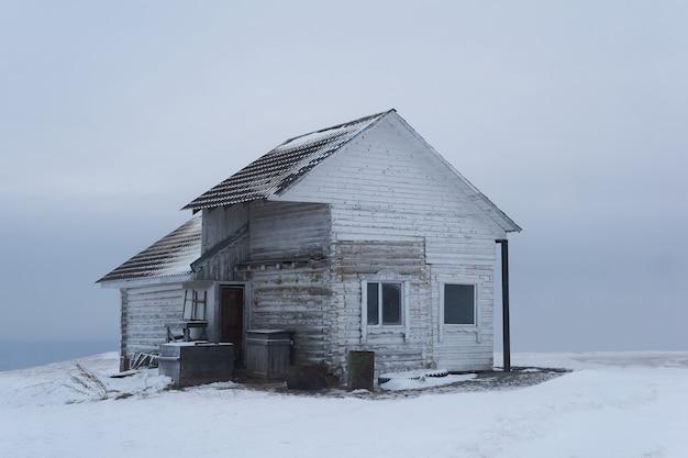 Vieille maison en bois au sommet d'une montagne dans un paysage déserté d'hiver enneigé