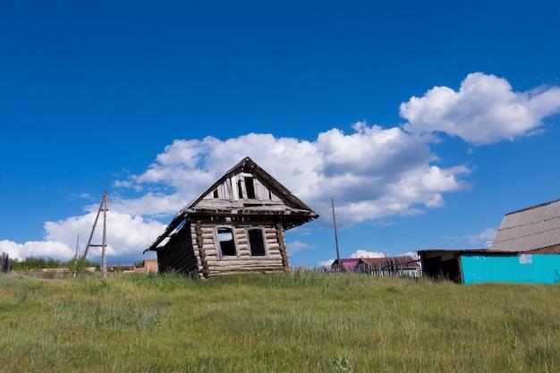 Vieille maison en bois en ruine sur le terrain