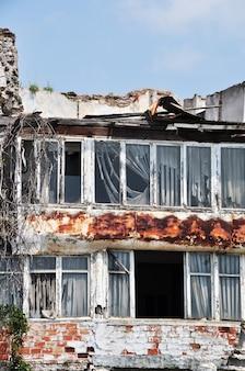 Vieille maison en brique. cadres de fenêtre sans verre. toiture métallique démontée.