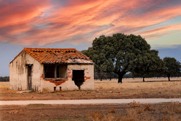 Vieille maison endommagée avec un beau ciel orange pendant le coucher du soleil