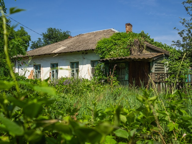 Vieille maison en ruine recouverte d'herbe épaisse. maison vide, qui a laissé des gens
