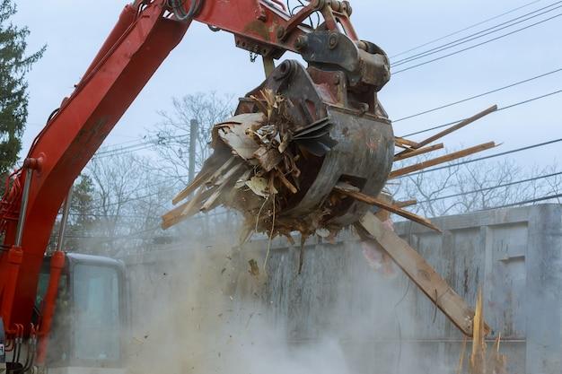 Vieille maison en train d'être démolie par une grosse pelle rétrocaveuse
