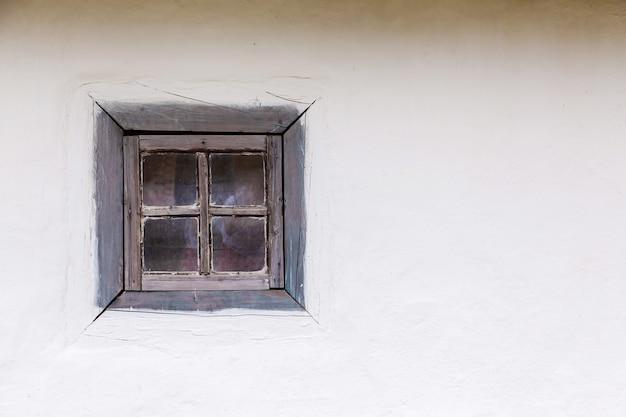Vieille maison ukrainienne avec une fenêtre en bois et un mur blanc