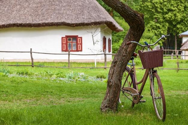 Vieille maison ukrainienne avec un toit de chaume et un vélo avec un panier près de l'arbre