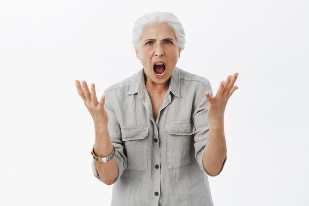Vieille mamie énervée en colère se serrant la main et criant, être en colère contre une personne
