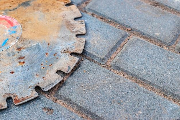 Une vieille meule à tronçonner en métal rouillé repose sur les dalles de pavage. fermer. outil de construction d'occasion.