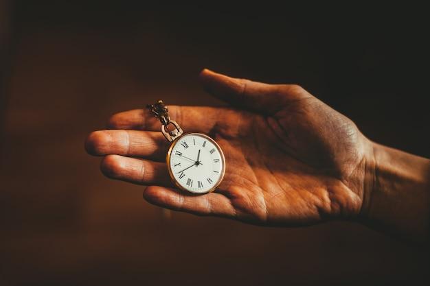 Une vieille montre dans la main de la fille. le concept du passé.