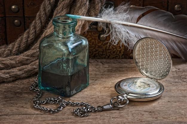 Vieille montre de poche et encrier, nature morte