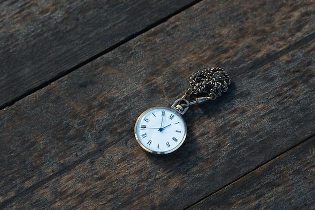 Vieille montre de poche sur fond de bois close up