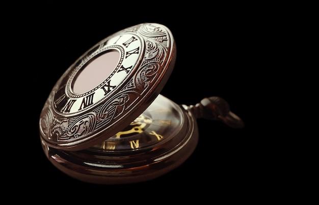 Vieille montre de poche sur fond noir