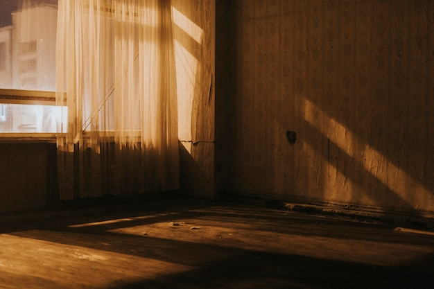 Vieille pièce vide avec des rideaux transparents