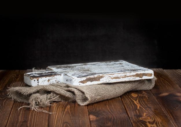 Vieille planche à découper en bois avec nappe en toile de jute